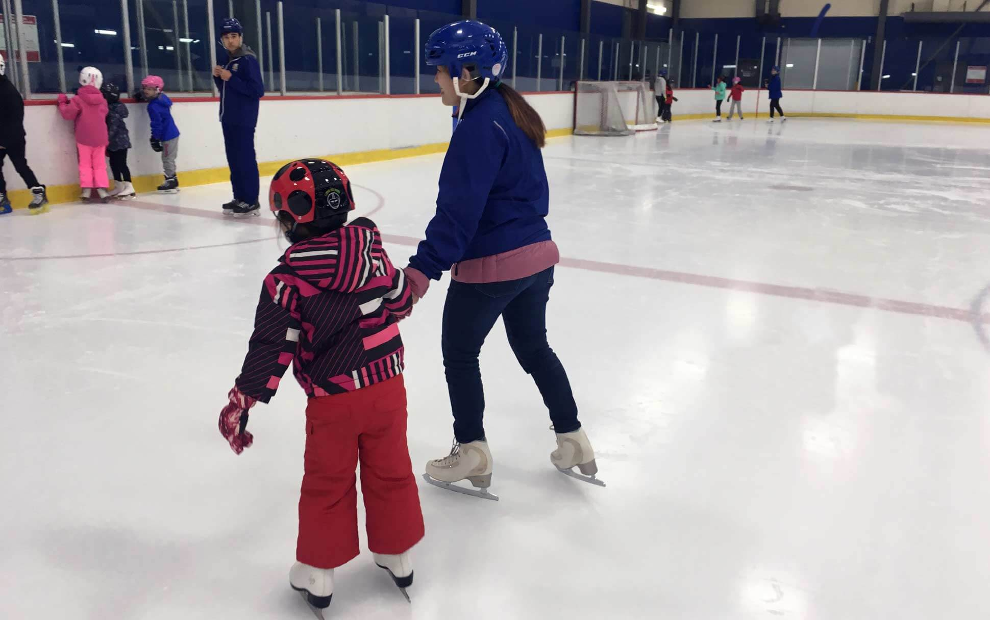 A woman and child skate on the ice rink at the Doug Mitchell Thunderbirds Sports Centre at UBC Vancouver.